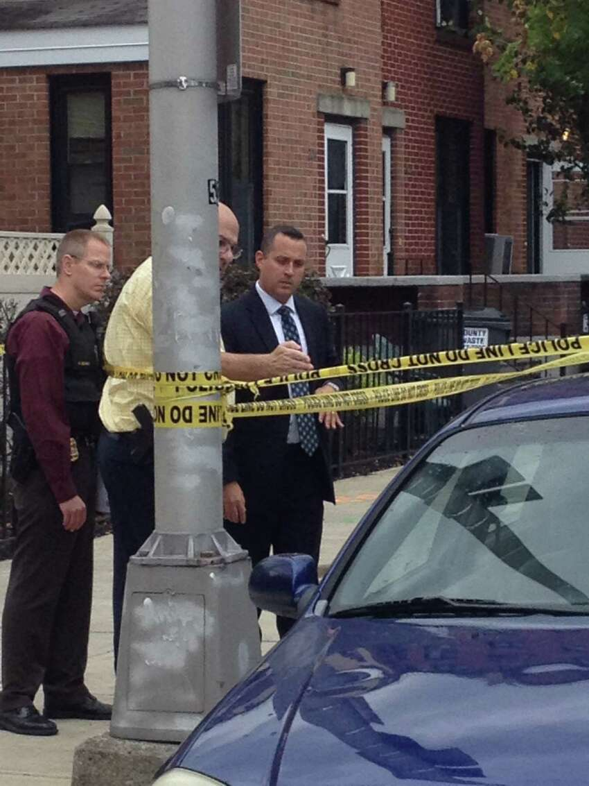 Police examine the an incident on Green Street where an officer's gun went off while police took a bank robbery suspect into custody Wednesday afternoon. (Brendan J. Lyons / Times Union)