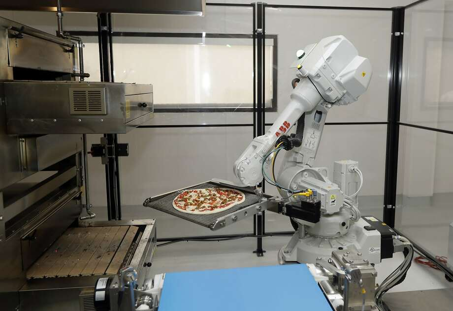 In this Monday, Aug. 29, 2016 photo, a robot places a pizza into an oven at Zume Pizza in Mountain View, Calif. The startup, which began delivery in April, is using intelligent machines to grab a slice of the multi-billion-dollar pizza delivery market. Zume is one of a growing number of food-tech firms seeking to disrupt the restaurant industry with software and robots that let them cut costs, speed production and improve worker safety.  (AP Photo/Marcio Jose Sanchez) Photo: Marcio Jose Sanchez, Associated Press