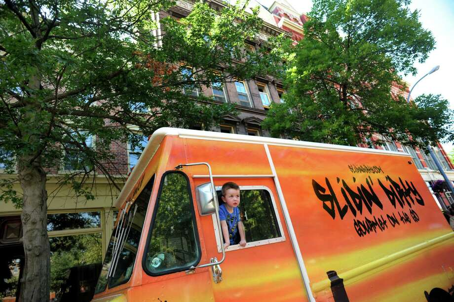 Ryan Taney, 3, looks out from the Slidin' Dirty food truck on Friday, June 27, 2014, in Troy, N.Y. His parents, Tim and Brooke Taney, will turn their mobile food business into a restaurant on the first floor of 9 First St., the building in the background. (Cindy Schultz / Times Union) Photo: Cindy Schultz / 00027531A