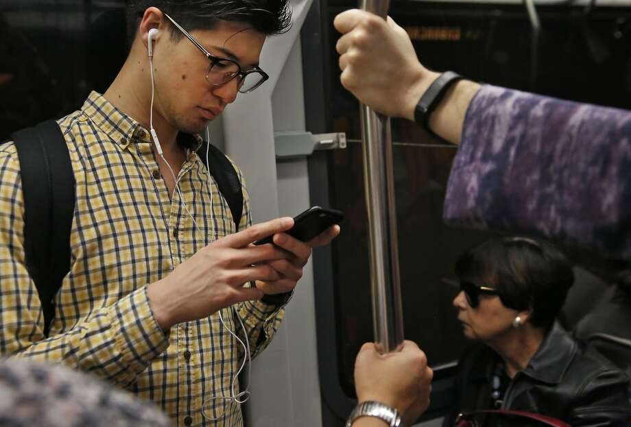 Jeff Korcal listens to a podcast and attempts to send texts as his phone service comes in and out while riding on the Muni L train Sept. 14, 2016 in San Francisco, Calif. Photo: Leah Millis, The Chronicle