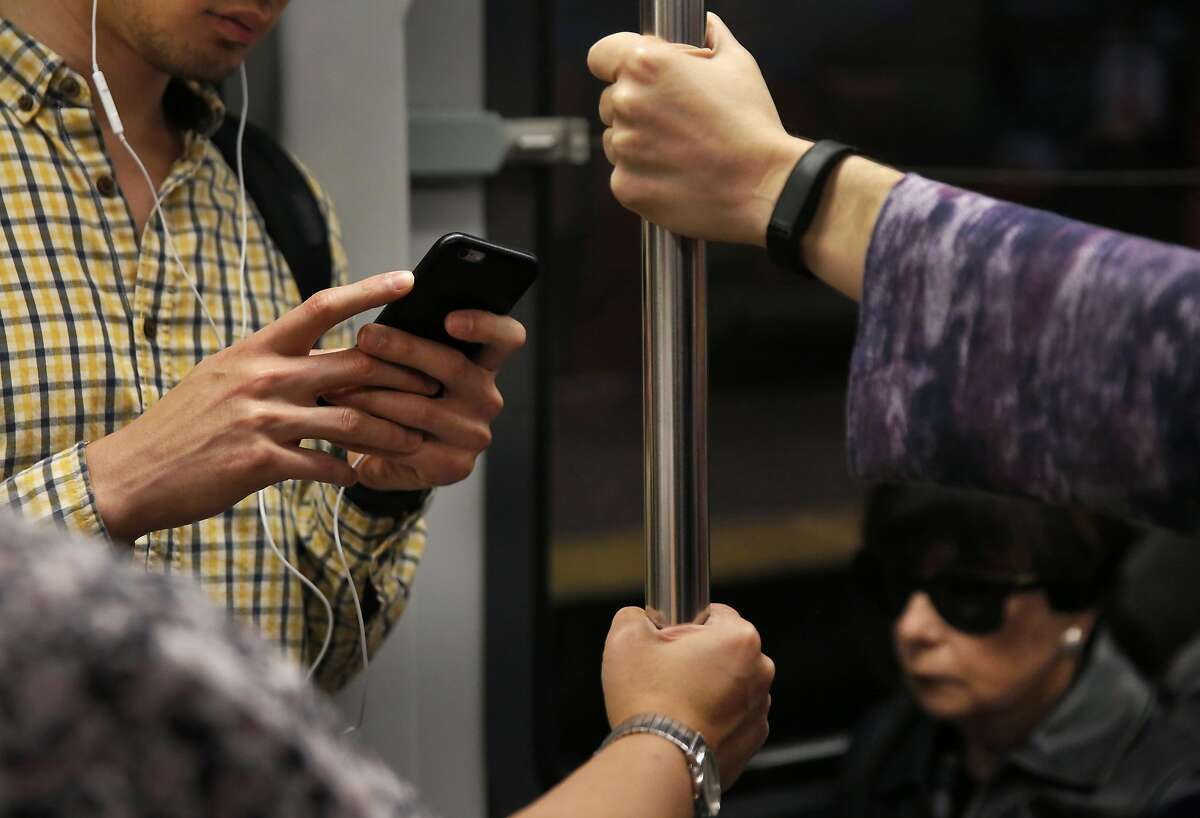 Jeff Korcal listens to a podcast and attempts to send texts as his phone service comes in and out while riding on the Muni L train Sept. 14, 2016 in San Francisco, Calif.