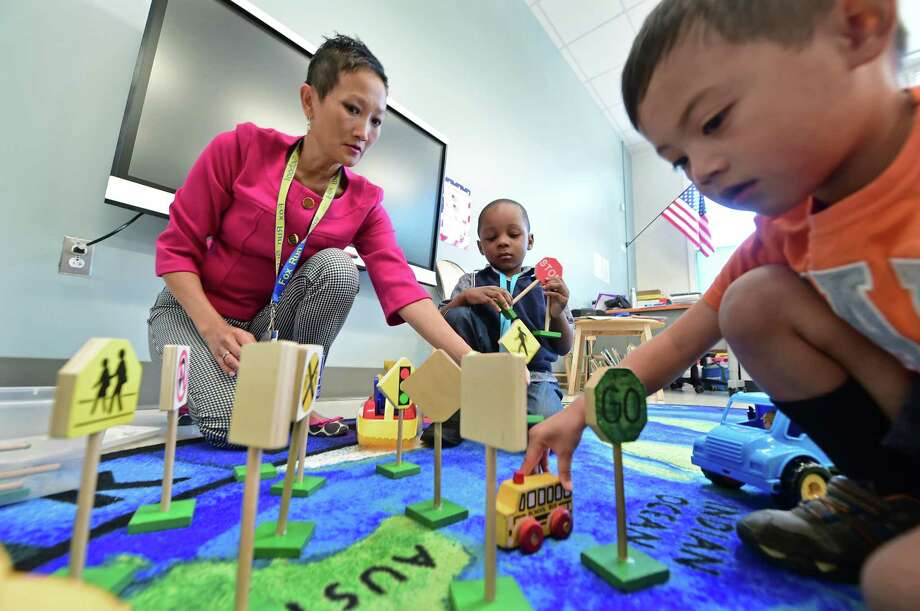 Norwalk Early Childhood Center paraprofessional, Sue Lynne Van Deventor, works with preschoolers, Dmitri Coiseau and David Valenton Wednesday, September 14, 2016, at the Center in Norwalk, Conn. The new Norwalk Early Childhood Center for special education and general education preschoolers, which held their grand opening ceremony Wednesday, consolidated eight Pre-K classrooms at five city schools to one location at the 11 Allen Road facility. Photo: Erik Trautmann / Hearst Connecticut Media / Norwalk Hour