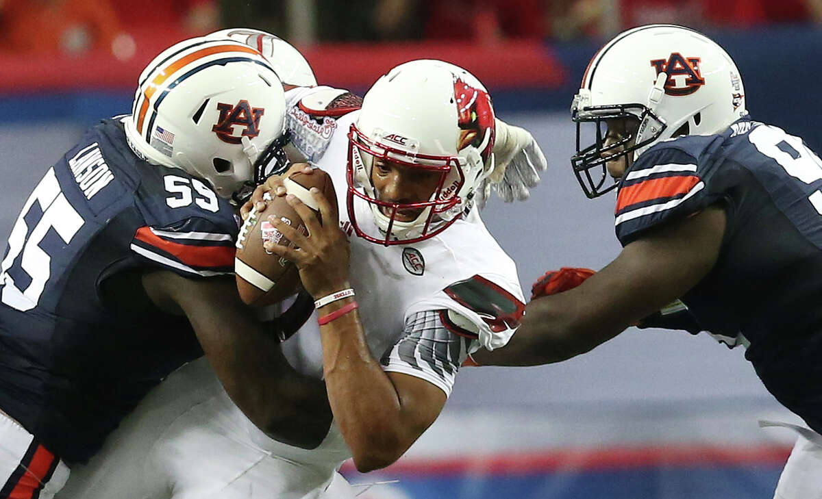FILe - In this Sept. 5, 2015, file photo, Auburn defensive lineman Carl Lawson (55) tackles Louisville quarterback Reggie Bonnafon (7) during the first half of an NCAA college football game, in Atlanta. Auburn's defensive line is one of the best in the Southeastern Conference, judging it solely on recruiting rankings. (AP Photo/John Bazemore, File)