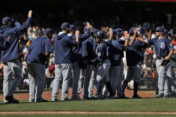 Padres teammates highfive on the infield after winning as the San Francisco Giants played the San Diego Padres at AT&T Park in San Francisco, Calif., on Wednesday, September 14, 2016. The Padres defeated the Giants 3-1, sweeping the series.