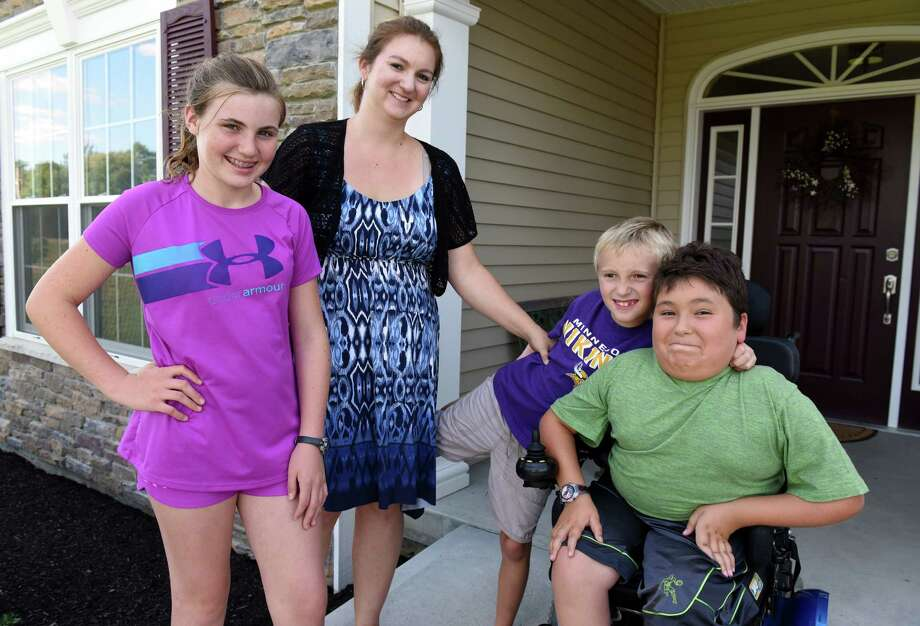 Step daughter Alyssia Bleau,11,  Amy Cunniff and her sons Zach, 8, and Caleb, 9, on Tuesday Sept. 13, 2016 in Duanesburg, N.Y. The family helps organize the annual Cure SMA (Spinal Muscular Atrophy) Walk-n-Roll in memory of Trooper David Cunniff. Caleb was diagnosed with SMA type II. This year's walk will be held on Saturday at the Colonie Mohawk River Park in Cohoes. (Michael P. Farrell/Times Union) Photo: Michael P. Farrell / 20037977A