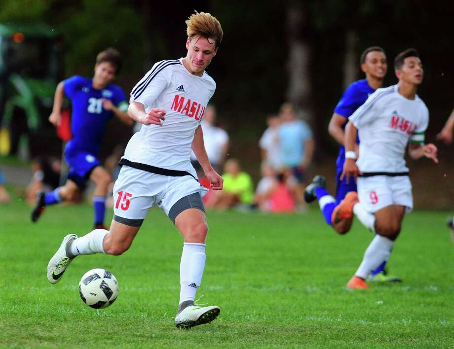 Masuk's Ryan Winkler drives the ball on his way to one of his two goals against Bunnell on Tuesday in Monroe. Photo: Christian Abraham / Hearst Connecticut Media / Connecticut Post