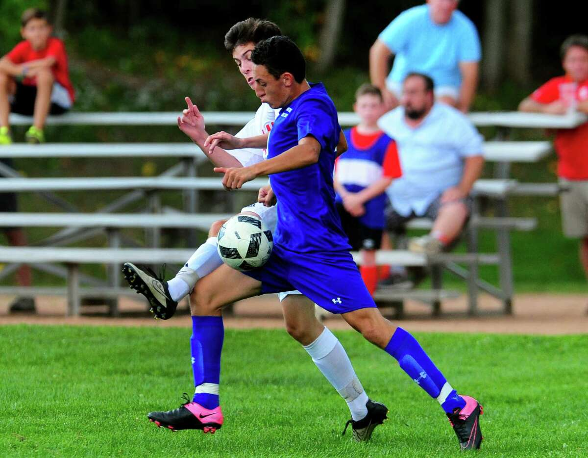 Masuk's Ryan Kristie leaps in front of Bunnell's Rafael Mesias to intercept the ball during boys soccer action in Monroe, Conn., on Wednesday Sept. 14, 2016.