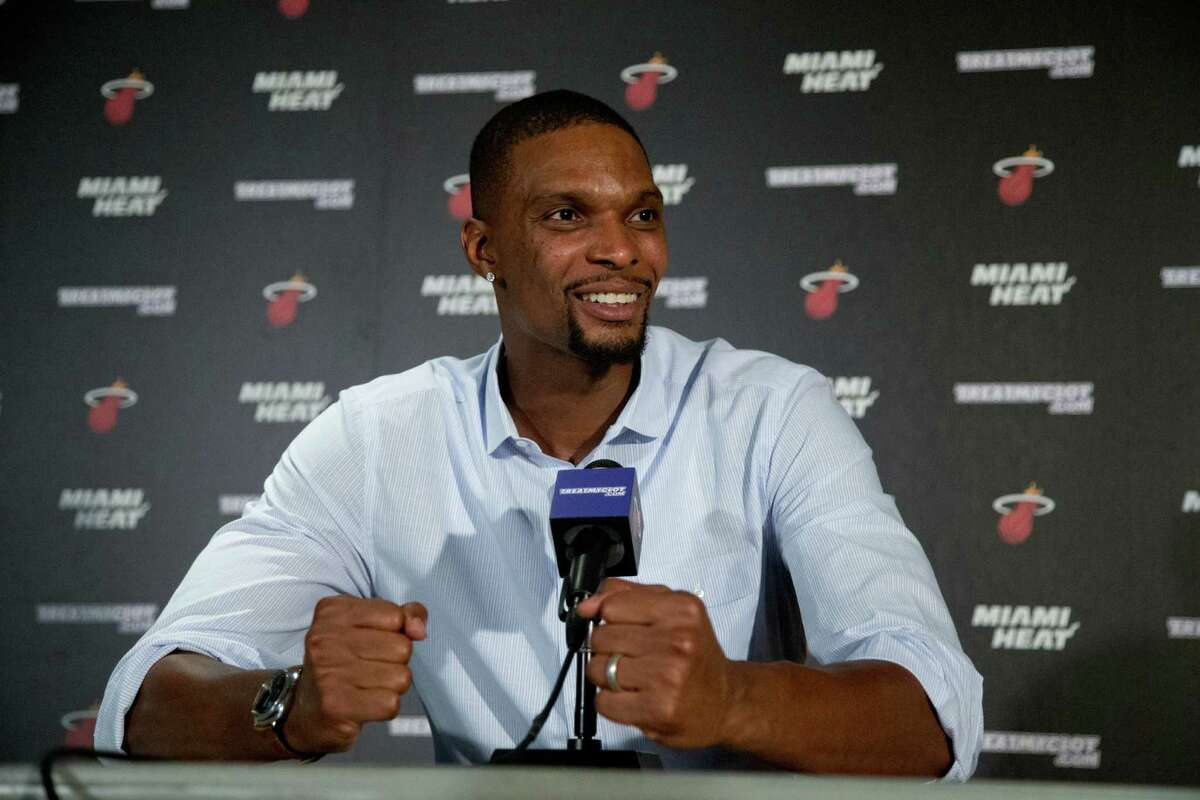 """FILE - In this Sept. 24, 2015, file photo, Miami Heat forward Chris Bosh gestures as he speaks during a news conference, in Miami. The Heat forward who had each of his last two seasons halted by blood clots that were discovered at the All-Star break said in a podcast released Wednesday, Sept. 14, 2016, that he """"absolutely"""" intends to be with his team for training camp that starts in the Bahamas on Sept. 27. But he also revealed that he has not yet been cleared to play again, though he's confident that it will happen. (AP Photo/Wilfredo Lee, File) ORG XMIT: NY174"""