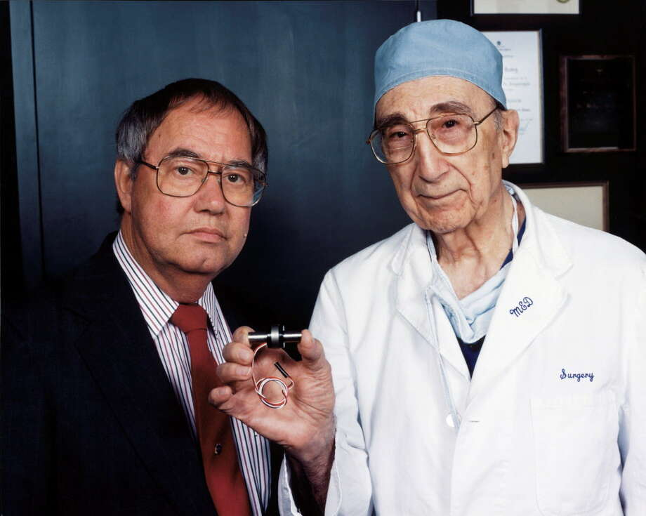 Dr. Michael DeBakey, right, displays a ventricular assist device - a tiny heart-assist pump -  that he designed.  / handout web