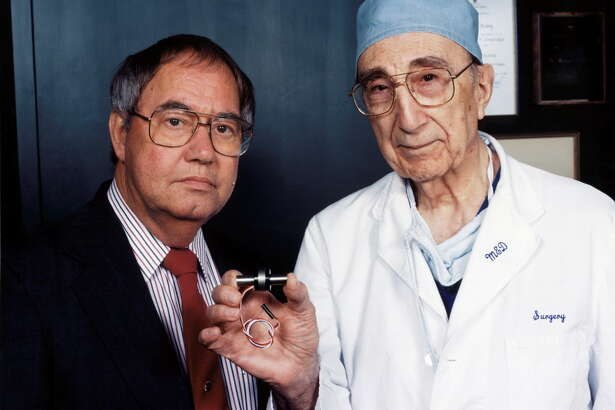 Dr. Michael DeBakey, right, displays a ventricular assist device - a tiny heart-assist pump -  that he designed.