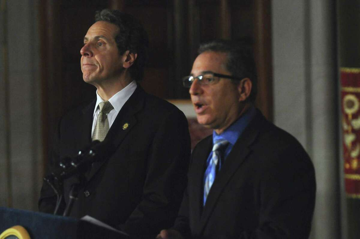 Governor Andrew Cuomo, left, listens as Director of Operations Howard Glaser, right, discusses PEF workers voting in favor of the state's contract proposal, thereby avoiding layoffs, in the Capitol on Thursday, Nov. 3, 2011, in Albany, N.Y. (Philip Kamrass / Times Union archive)