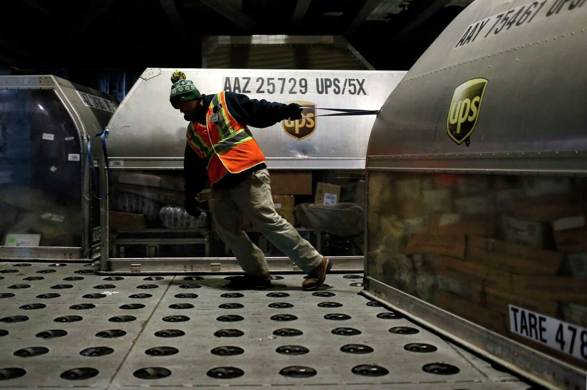 FILE - In this Nov. 20, 2015, file photo, a UPS worker pulls a container full of packages across a floor embedded with casters at Worldport in Louisville, Ky. UPS plans to add 95,000 workers to meet the 2016 holiday-season demand from online shopping, the company announced Wednesday, Sept. 14, 2016. That's about the same as in 2015. (AP Photo/Patrick Semansky, File) ORG XMIT: NYBZ304