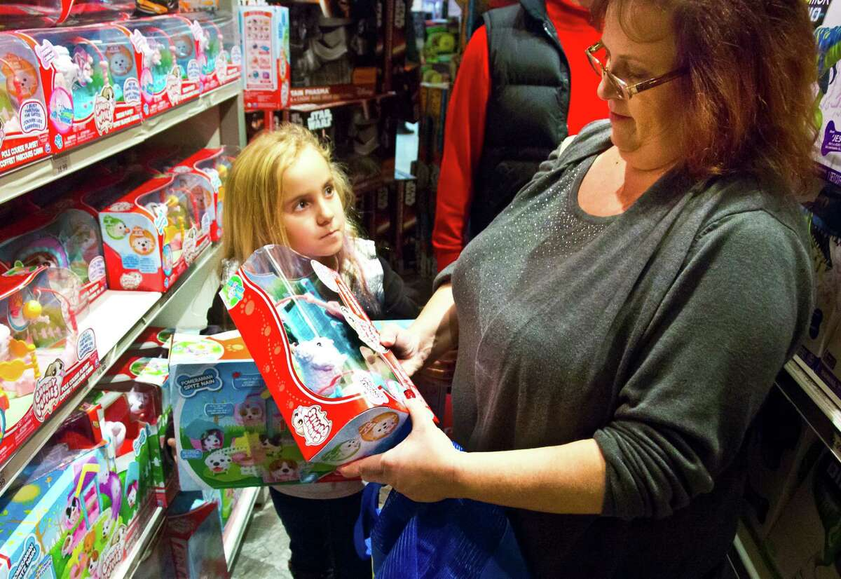 """FILE - In this Friday, Nov. 27, 2015, file photo, Cinnamon Boffa, right, from Bensalem, Pa., checks out a """"Chubby Puppies"""" toy for her daughter Serenity, left, at a Toys R Us, in New York. Toys R Us said Wednesday, Sept. 14, 2016, it has begun taking applications for part-time seasonal jobs in stores and distribution centers. A spokeswoman declined to give a nationwide figure but said the retailer expects to add at least 10,900 workers in five of its biggest markets: New York, Los Angeles, Philadelphia, Chicago and Washington. (AP Photo/Bebeto Matthews, File) ORG XMIT: NYBZ305"""