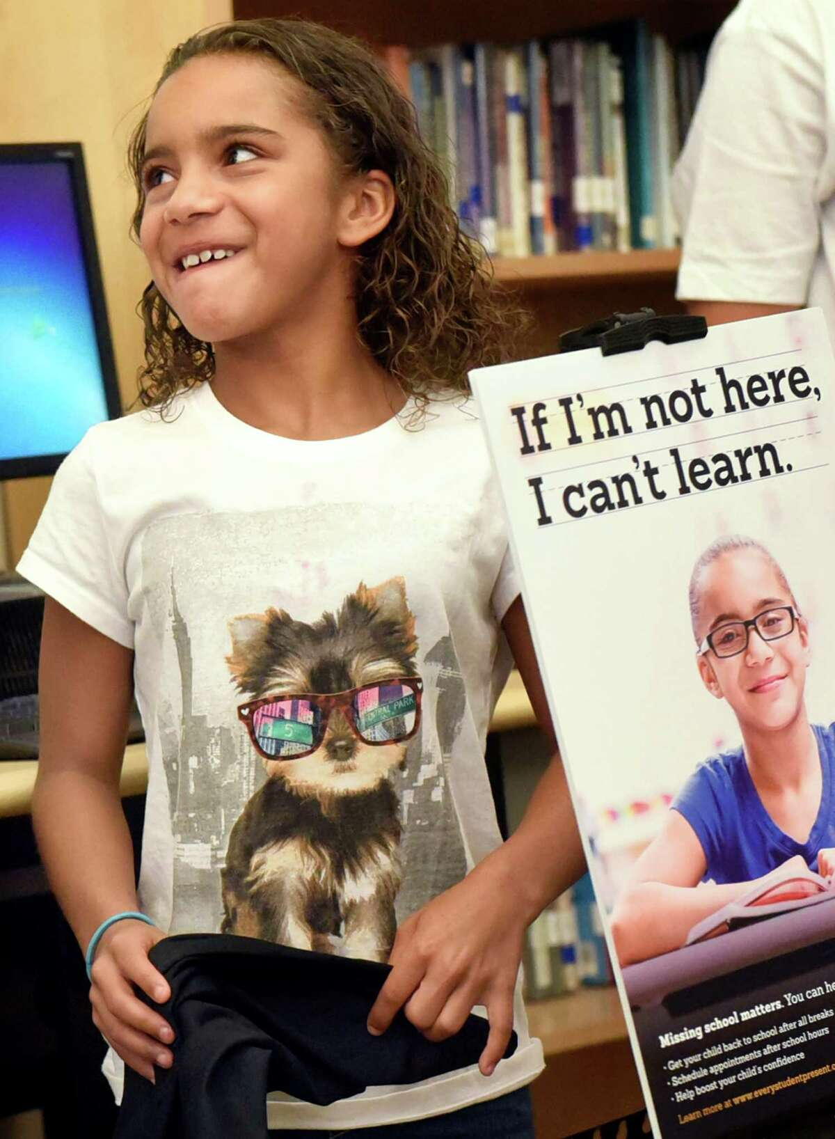 Sanai Valentin, 9, grins once she unveils a poster of her likeness for a statewide campaign focusing on school attendance on Wednesday, Sept. 14, 2016, at Pine Hills Elementary in Albany, N.Y. The Every Student Present campaign will include posters and public service announcements throughout the state, a parent resource website and a community tool kit. (Cindy Schultz / Times Union)