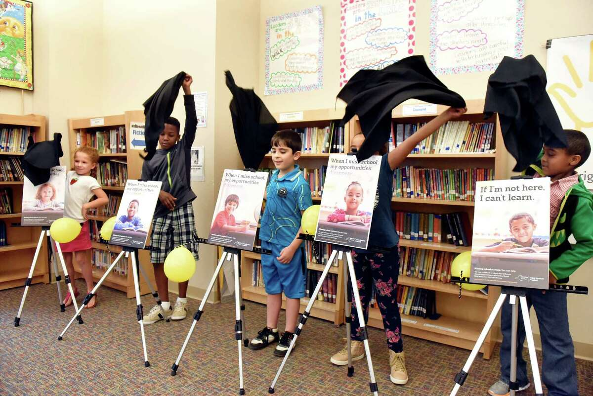 Students unveil posters of themselves for a statewide campaign focusing on school attendance on Wednesday, Sept. 14, 2016, at Pine Hills Elementary in Albany, N.Y. From left are Emma Kraus, 7, Ty Simpson, 10, Basem Muhi, 9, Ke'asia Heath-LaChance, 8, and Abdulaziz Omar, 8. The Every Student Present campaign will include posters and public service announcements throughout the state, a parent resource website and a community tool kit. (Cindy Schultz / Times Union)
