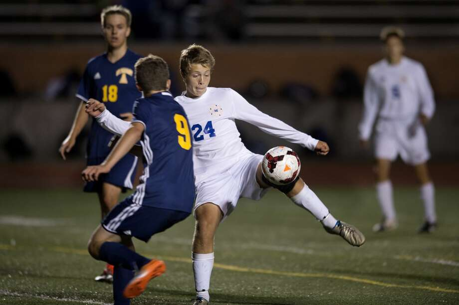 Midland High's Andrew Bott kicks the ball away from Mount Pleasant's Lucien Stairs in the second half of Midland's home game Wednesday evening. Midland defeated Mount Pleasant 5-1. Photo: Brittney Lohmiller/Midland Daily News/Brittney Lohmiller, Brittney Lohmiller/Midland Daily News