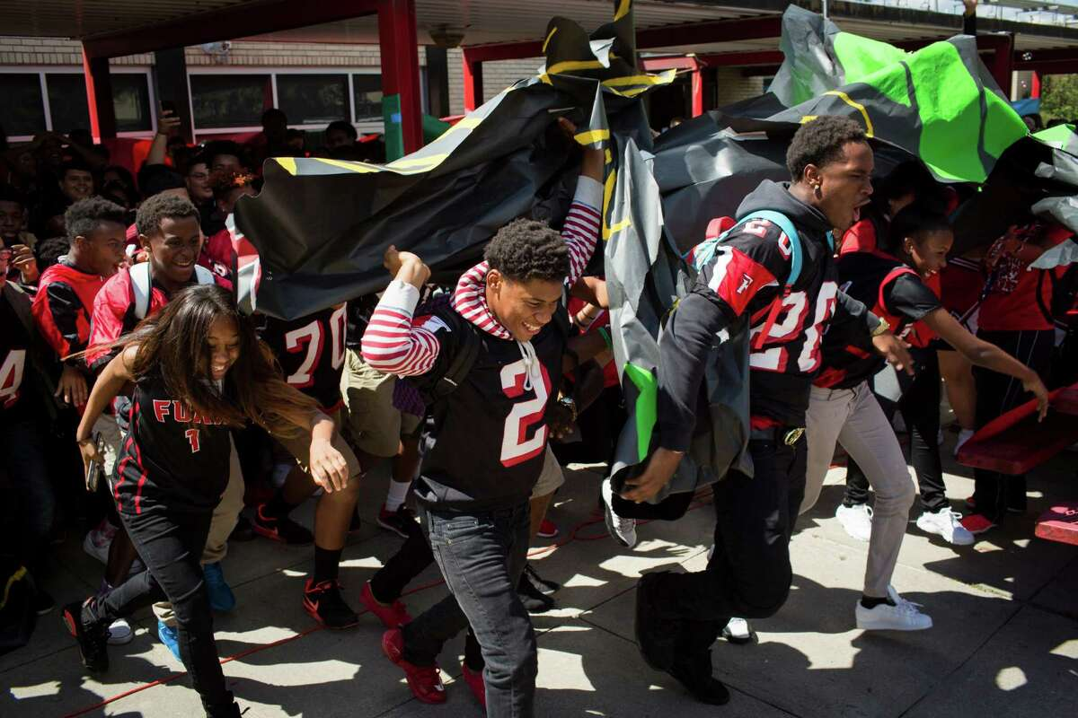 Furr football players Lance Clark and Reginald Robinson lead students to the award celebration.