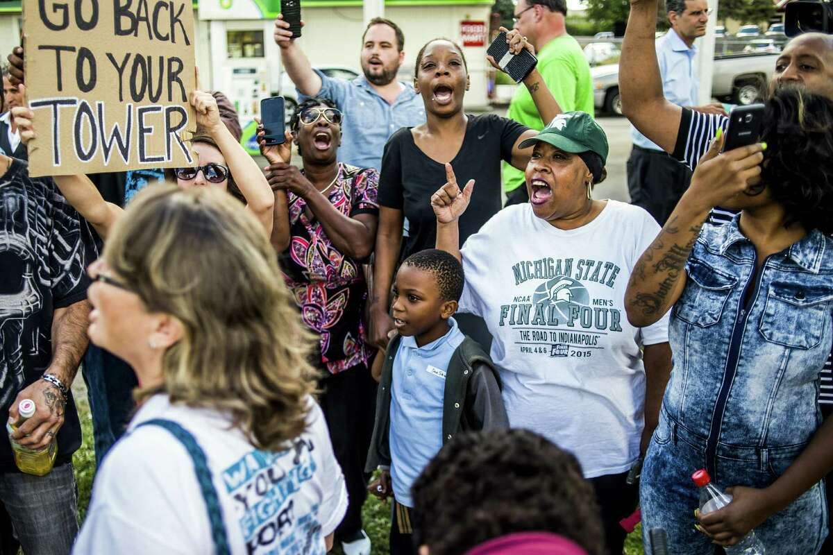 Flint residents Josephine Thornton Melva Lewis and Juanita Young-Wells, left to right in center, shout out in unison as they chant against Donald Trump at a gas station at the intersection of Dort Highway and Stewart Avenue, where more than 100 people gather to support, protest and just try and catch a glimpse of the Republican presidential candidate on Wednesday, Sept. 14, 2016 as his caravan drops him off for a tour of the Flint Water Plant in Flint, Mich. (Jake May/The Flint Journal-MLive.com via AP) ORG XMIT: MIFLI101