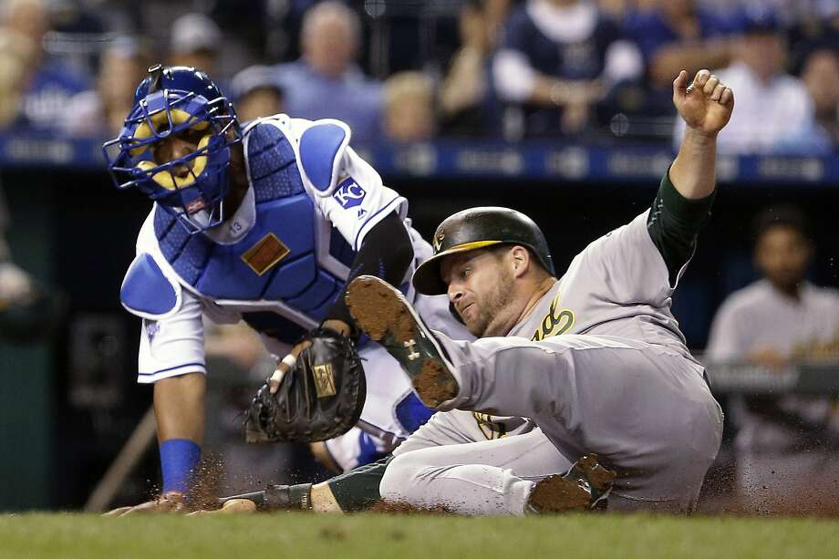 A's designated hitter Stephen Vogt beats the tag by Royals catcher Salvador Perez to score in the eighth inning. Photo: Charlie Riedel, Associated Press