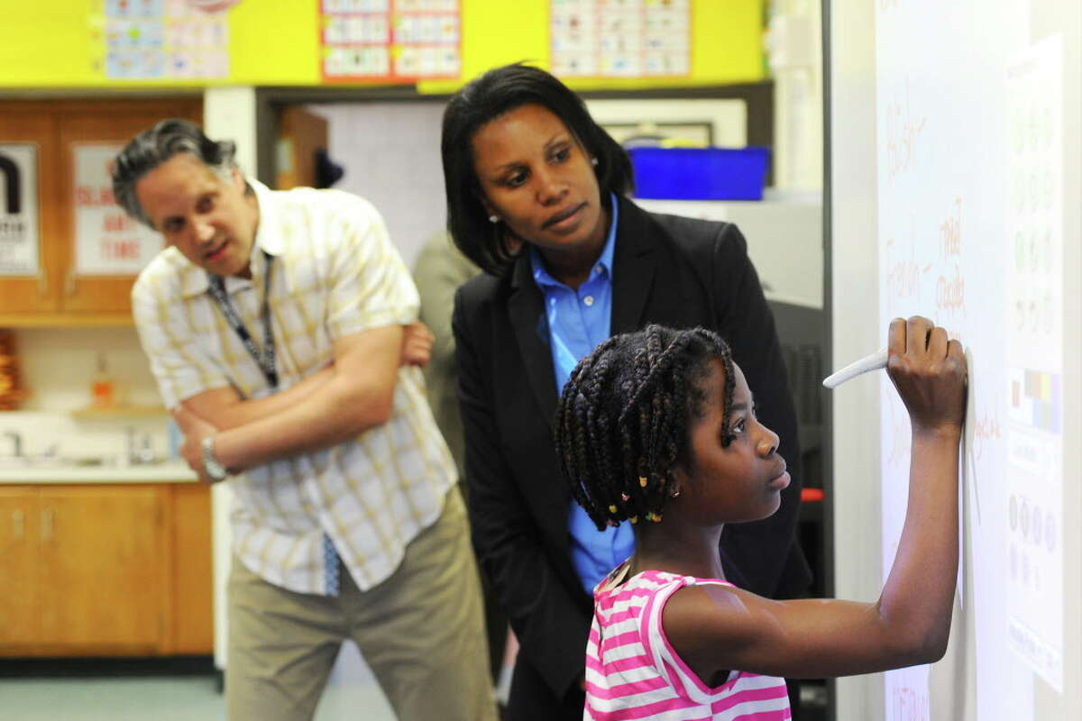 FILE - Nine-year old Akouvi Migah writes the word for hello in her native French while instructor Marius Popescu (left) and Dr. Tamu Lucero look on inside Davenport Elementary School's English Language Learners program on Tuesday, June 7, 2016.