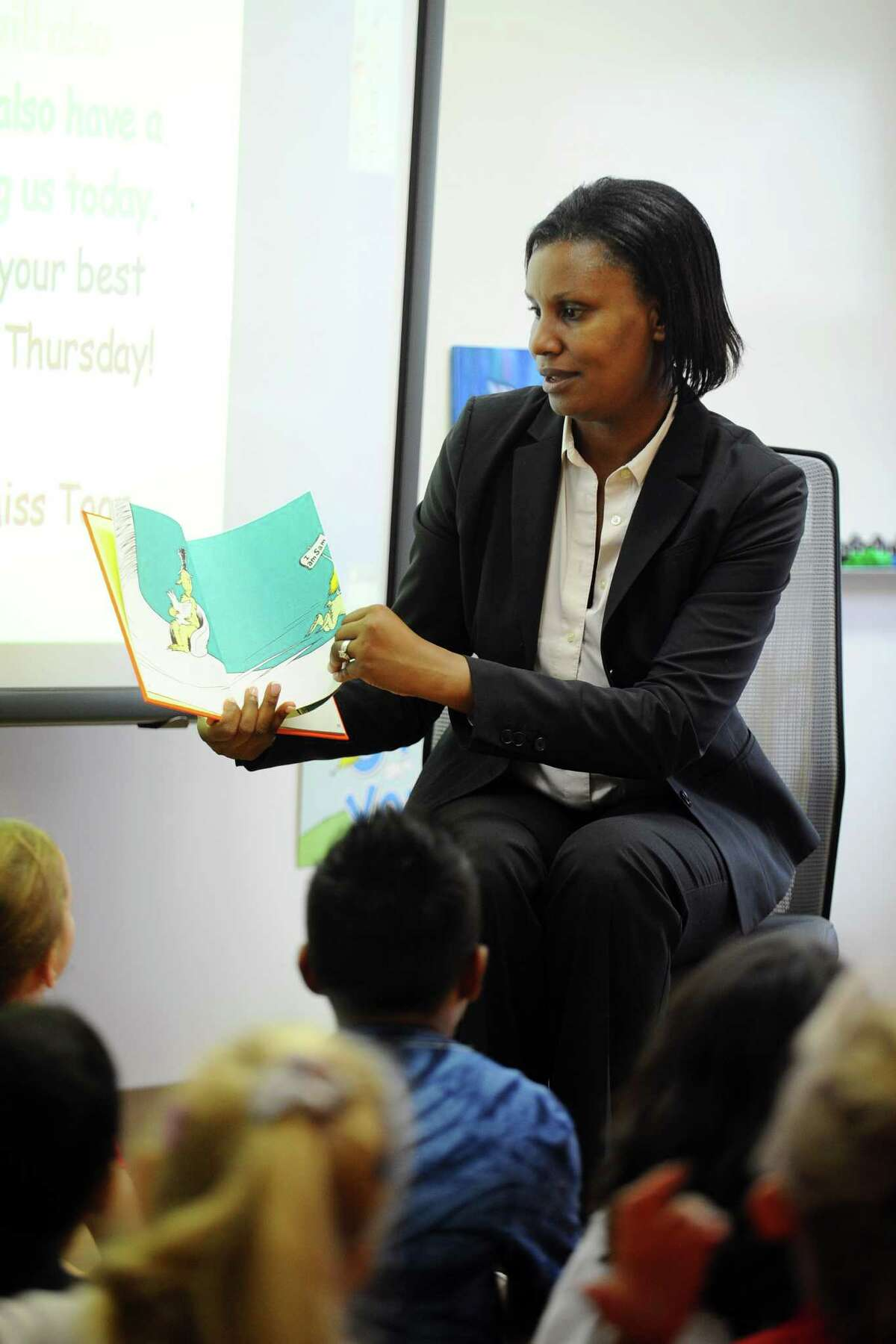 FILE - Assistant Superintendent Dr. Tamu Lucero reads a Dr. Seuss book to a first grade class at the New School, on Strawberry Hill Ave. in Stamford, Conn., on Thursday, September 1, 2016.
