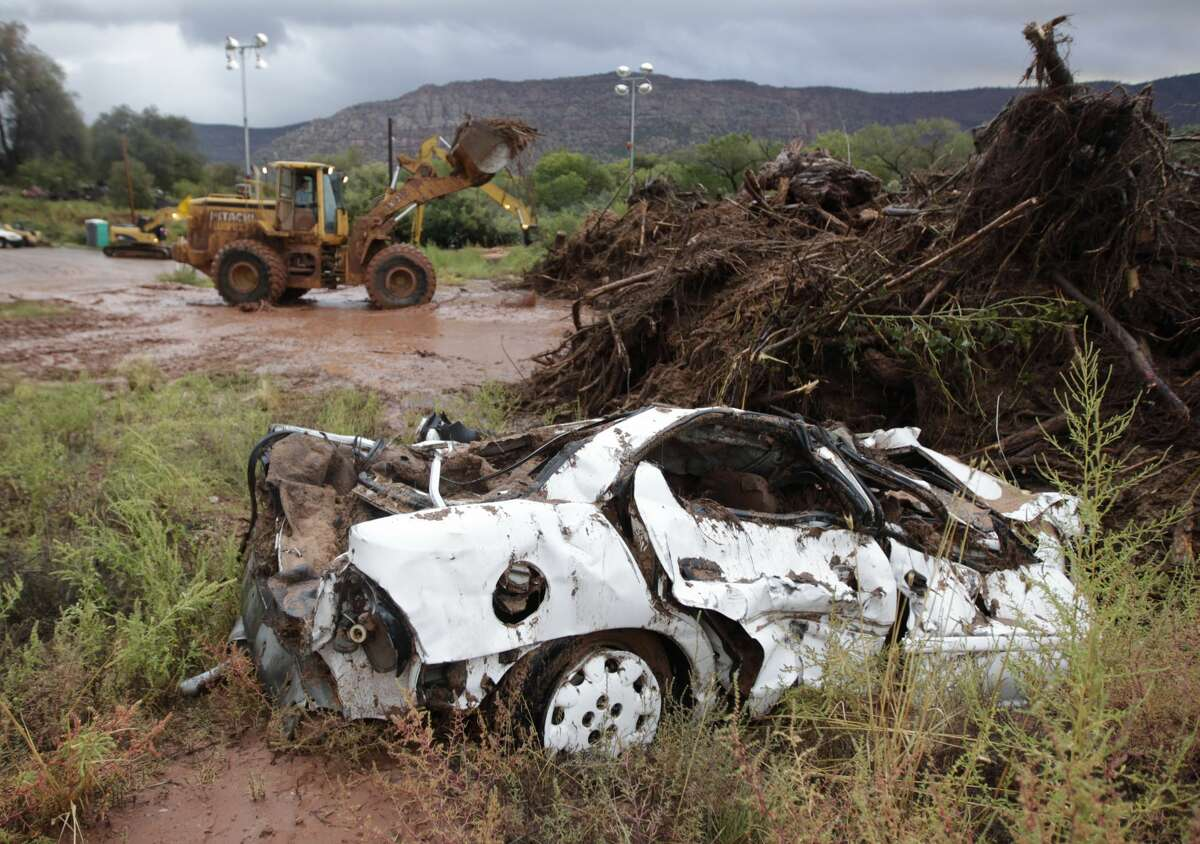 COLORADO CITY, AZ - SEPTEMBER 15: A car sits along the side of Short Creek along with other debris after being removed from the creek on September 15, 2015 in Colorado City, Arizona. Flash floods from heavy rains on the afternoon of September 14, 2015 washed away two cars in Hildale as they were crossing a flooded creek, killing 8 people with five still missing. (Photo by George Frey/Getty Images)