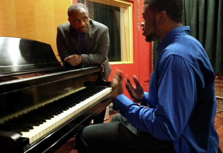 Tony Thompson, left, talks with musician Justin Murray as he records music for a planned Christmas album. Murray, 19, is recording in Thompson's studio at Kwame Building Group. The studio is part of Thompson's foundation's efforts to provide opportunities to minorities.