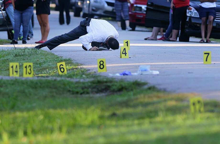 A detective investigates the scene of an early morning drive-by shooting that left one woman dead and three men injured, Thursday, Sept. 15, 2016. Photo: Houston Chronicle / © 2016 Houston Chronicle