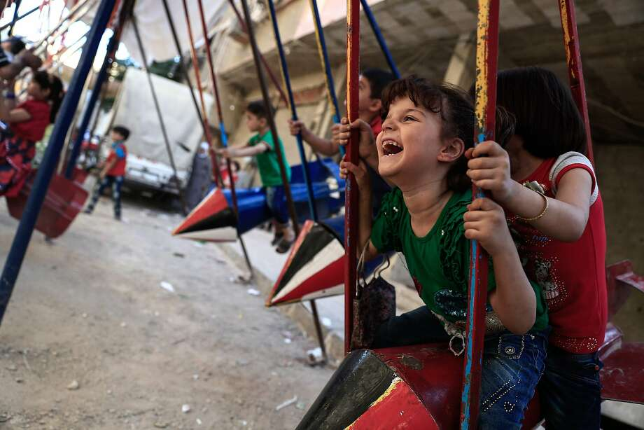 Children play on swings, made from the remnants of exploded rockets, in the rebel-held town of Douma. Photo: SAMEER AL-DOUMY, AFP/Getty Images