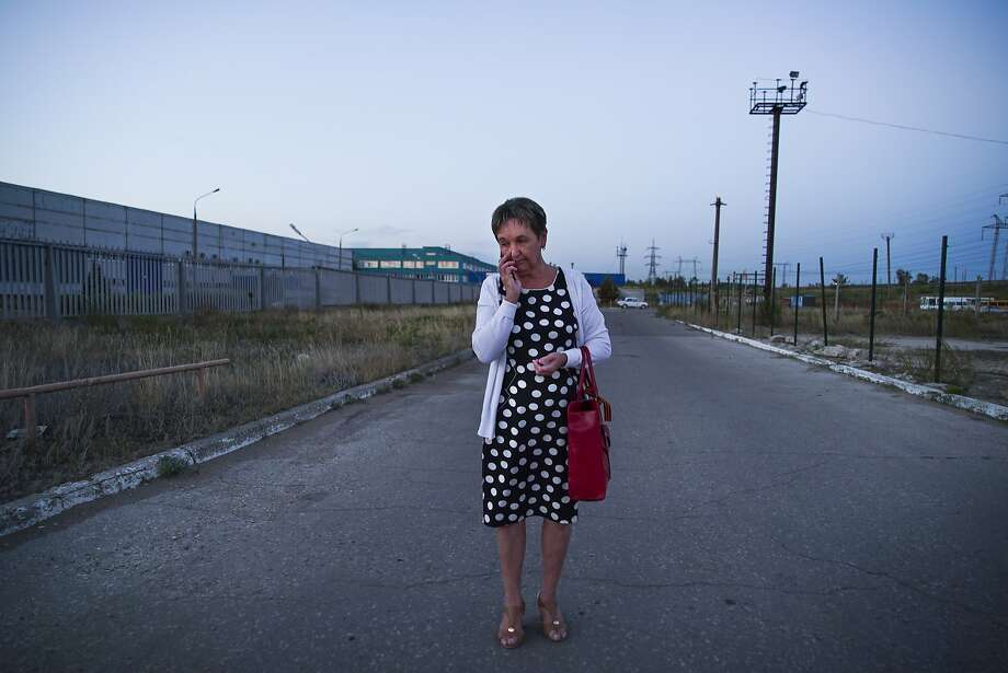 A woman walks by the closed factory in Togliatti where she worked before AvtoVAZagregat went bankrupt. The factory once produced seats and other interior components for cars. Photo: Mstyslav Chernov, Associated Press