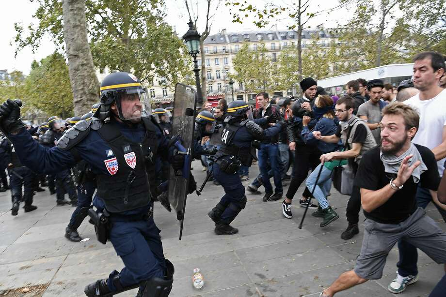 Paris police charge opponents of labor reforms adopted this summer that allows employers more freedom to extend workweeks and lay off staff. Police fired tear gas and stun grenades. Photo: CHRISTOPHE ARCHAMBAULT, AFP/Getty Images