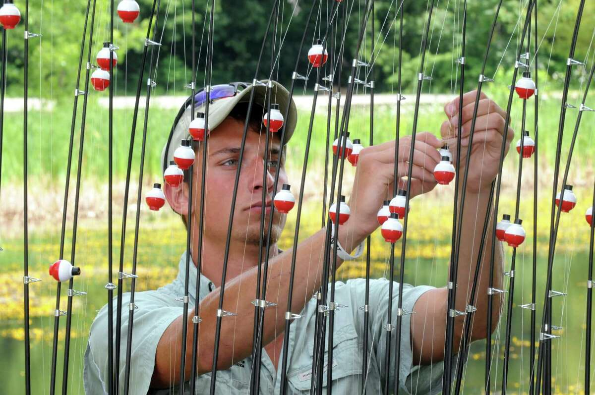 DEC intern Brandon Winter readies fishing pools for children during a festival to celebrate the improvements at Steinmetz Park and begin a new tradition for Goose Hill residents on Saturday July 25, 2015 in Schenectady, N.Y. (Michael P. Farrell/Times Union)