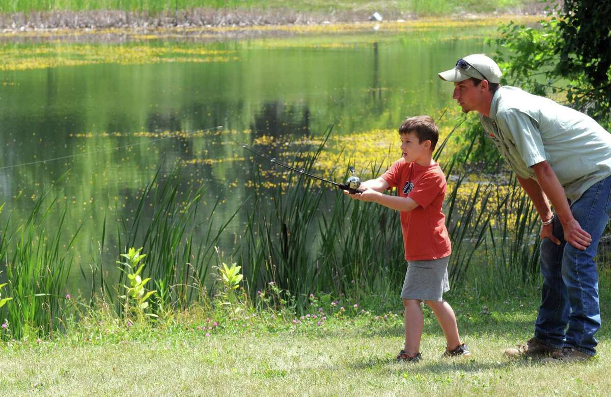 DEC intern Brandon Winter helps six-year-old Noah Wright with his fishing pool casting during a festival to celebrate the improvements at Steinmetz Park and begin a new tradition for Goose Hill residents on Saturday July 25, 2015 in Schenectady, N.Y. (Michael P. Farrell/Times Union)