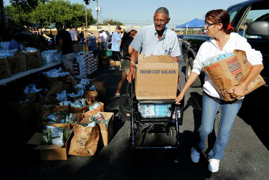 Charles Pate, 72, receives assistance from volunteer Theresa Ellard in picking up food at Windcrest United Methodist Church on Thursday, Sept. 15, 2016. Once a month, the church serves as a pickup location for people in need of food. Through funding from the Texas Diaper Bank, the church provides a location and manpower for the San Antonio Food Bank to drop off nutritional foods to be distributed to about 100 households. Nearly 30 volunteers gathered to help distribute the food to recipients like Pate. The Vietnam veteran said he has come out to the Windcrest church to get food for the past three to four years. The supply usually lasts about two weeks, Pate said. Photo: Kin Man Hui /San Antonio Express-News / ©2016 San Antonio Express-News