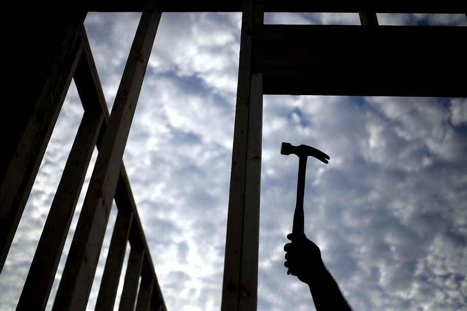 The silhouette of a contractor is seen hammering wood framing for a house under construction in the Louisville, Ky. Photo: Luke Sharrett, Bloomberg