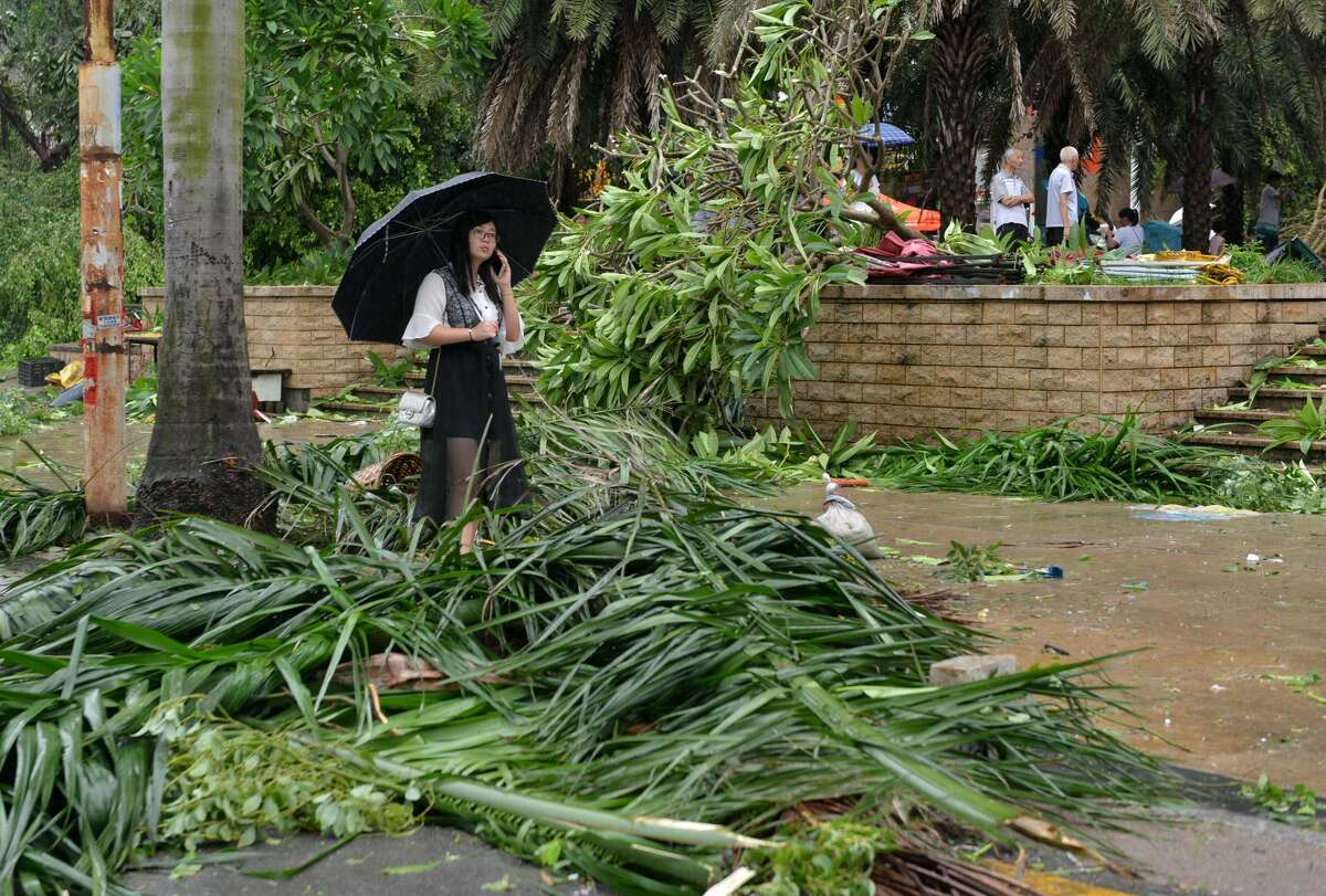 TOPSHOT - A woman stands amid downed tree branches on a street in Xiamen, China's eastern Fujian province, after Typhoon Meranti made landfall on September 15, 2016. Typhoon Meranti made landfall in Fujian early September 15 with winds up to 230kph, knocking out electricity in some areas and causing rail delays. / AFP / STR / China OUT (Photo credit should read STR/AFP/Getty Images)