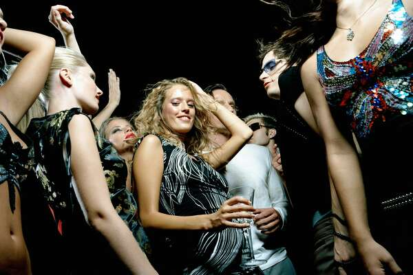 Young woman dancing in crowd of people, portrait, low angle view