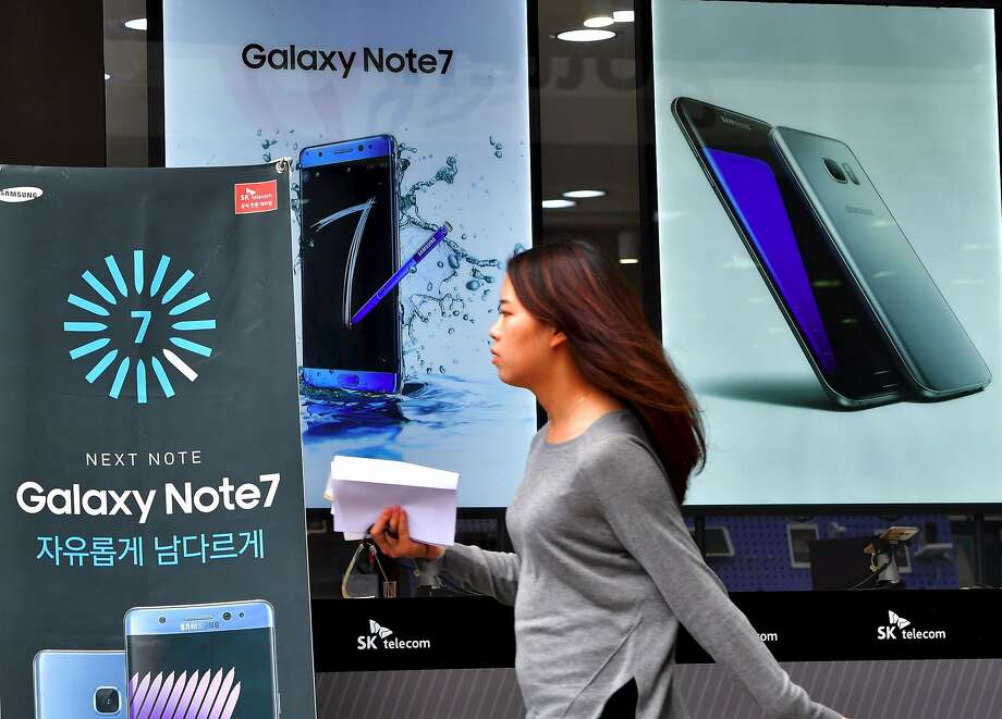 A woman walks past billboards of Samsung Galaxy Note 7 (L) and Galaxy S7 (R) at a mobile phone shop in Seoul on September 12, 2016. Samsung shares plunged on September 12 after the South Korean electronics giant urged global users to stop using its Galaxy Note 7 smartphone due to a spate of exploding batteries that raised alarm around the world. / AFP PHOTO / JUNG YEON-JEJUNG YEON-JE/AFP/Getty Images Photo: JUNG YEON-JE, AFP/Getty Images