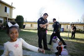 While on foot patrol, Officer Perino, left, and Officer Carducci stop and  talk with Jayon Evans, 4, and Nevaeh Frazier, 4, left, as they draw on the sidewalk with chalk in the San Pablo Housing Projects in San Pablo, CA, Tuesday, January 14, 2014.   San Pablo, CA, with a population of 30,000, had zero homicides last year, due in part to the police taking a more active role in the community with increased foot patrols, interactions with citizens and youth programs.