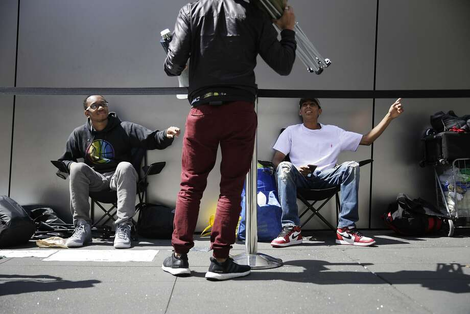 Justin Harris (left) of Oakland and Miguel Hernandez (right) of Stockton participate in the recording of an CNET Apple Byte segment with host Brian Tong (center) as they wait in line outside the Apple Store in Union Square on Thursday September 15,  2016 in San Francisco,  California. Photo: Lea Suzuki, The Chronicle