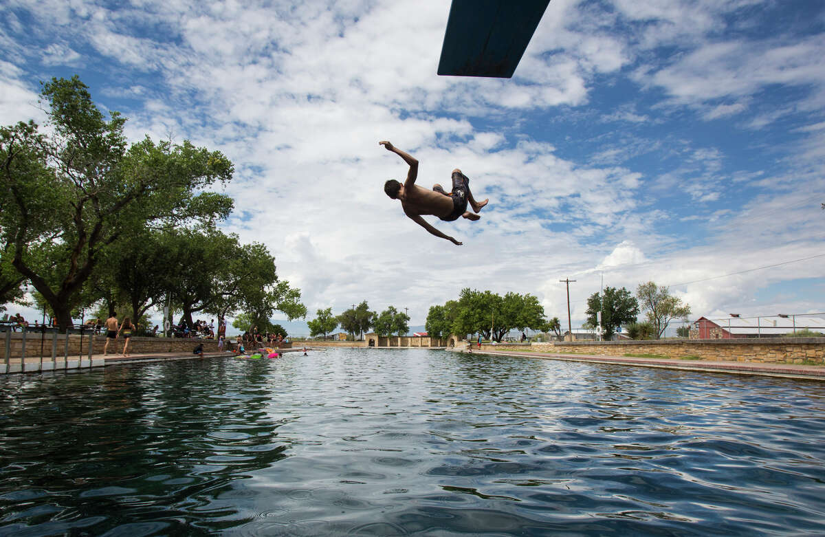 ADVANCE FOR WEEKEND EDITIONS AUG. 27-28 - In this Aug. 18, 2016 photo, a boy jumps off the diving board into 30 feet of water at the natural spring pool at the Balmoreah State Park in Balmoreah, Texas. The rise of fracking nearby the town has some community members worried about their drinking water and natural springs, which serve as a popular tourism destination helping drive the town's economy. (Brittany Greeson/The San Antonio Express-News via AP)