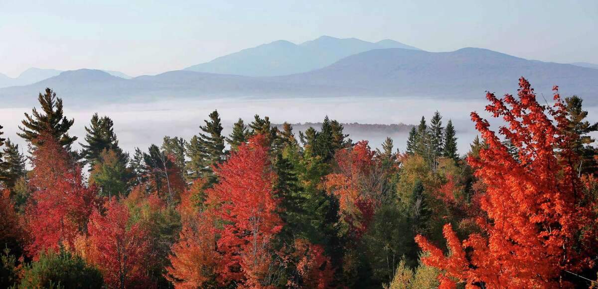 Fog sits in the valley of the White Mountains as leaves change colors from Milan Hill in Milan, N.H.