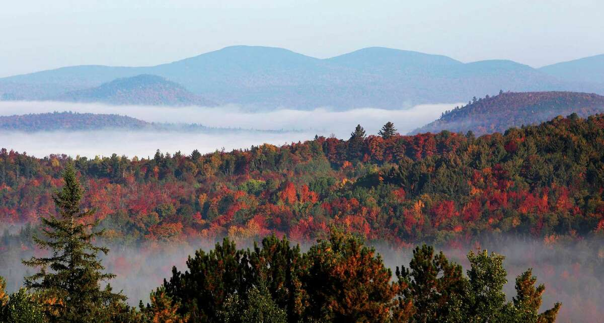 Fog sits in the valley of the White Mountains in late September of 2014 as leaves change colors, in this photo taken from Milan Hill in Milan, N.H.