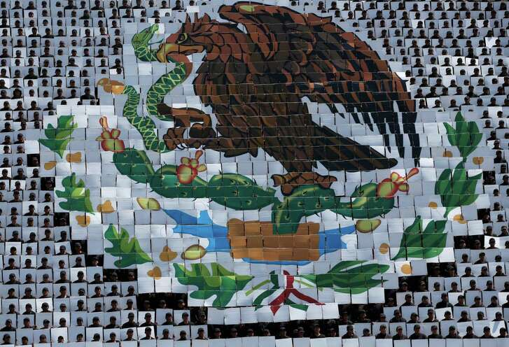Hundreds of military troops hold cards making a mosaic depiction of the Mexican coat of arms, an eagle catching a serpent while standing atop a cactus, during a review of the troops that will march in the Independence Day parade, in Mexico City, Wednesday, Sept. 14, 2016. Thousands will gather in Mexico City's main square known as the Zocalo on Friday for a massive military parade to commemorate Mexico's independence from Spain.(AP Photo/Rebecca Blackwell)