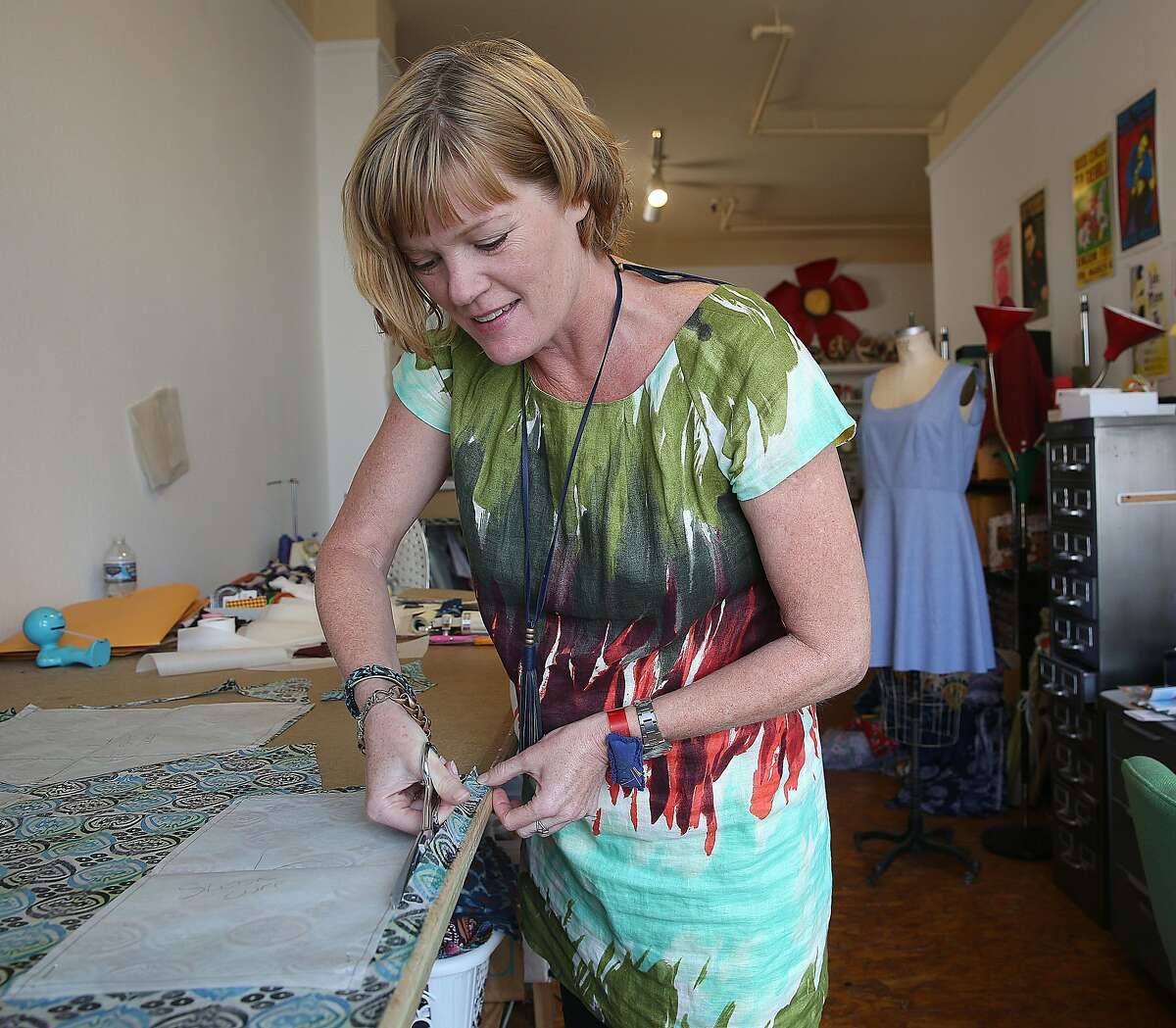 Clothing designer Dema Grim in her downtown studio as she cuts a pattern on Tuesday, September 13, 2016, in San Francisco, Calif.