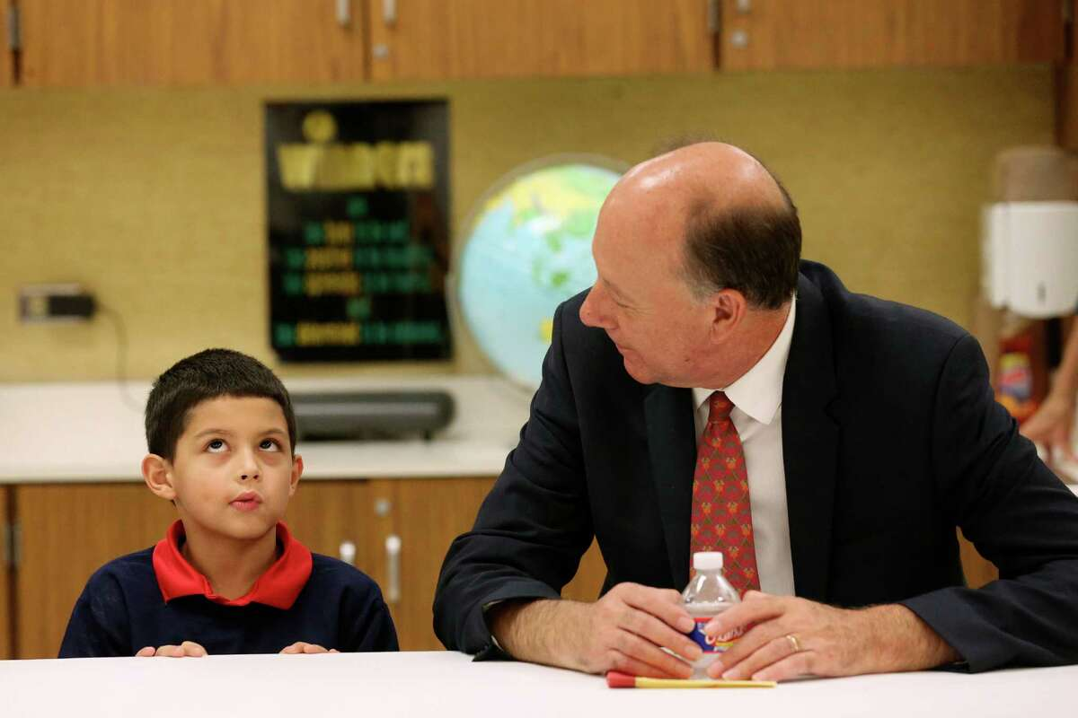 Johan Uvin, acting U.S. assistant secretary for career, technical and adult education, talks with Bowden Elemenatry School second-grader Brandon Garza-Roldan, 7, during a tour of the school.