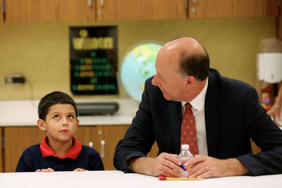 Johan Uvin, acting U.S. assistant secretary for career, technical and adult education, talks with Bowden Elemenatry School second-grader Brandon Garza-Roldan, 7, during a tour of the school. Photo: Photos By Jerry Lara / San Antonio Express-News / © 2016 San Antonio Express-News