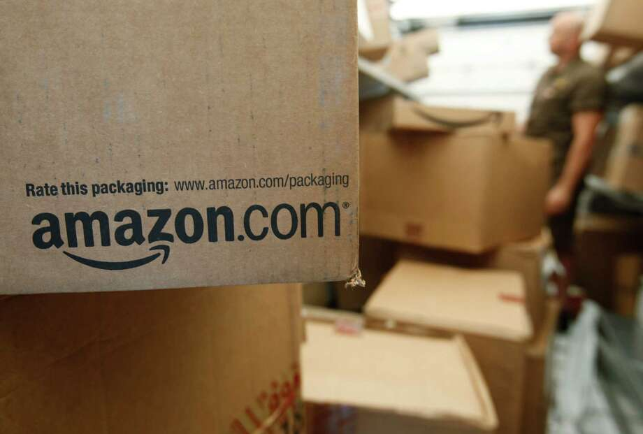 FILE - In this Oct. 18, 2010 file photo, an Amazon.com package awaits delivery from UPS in Palo Alto, Calif. Amazon is suing more than 1,000 people for advertising their services writing fake reviews for as little as $5 as it seeks to crack down on bogus reviews on its site. The complaint filed Friday, Oct. 16, 2015 in King County Superior Court in Seattle marks the latest effort by the online powerhouse to crack down on fraud on its site. (AP Photo/Paul Sakuma, File) Photo: Paul Sakuma, STF / AP