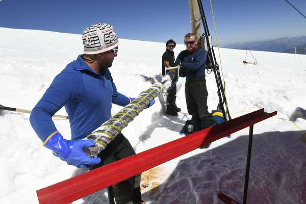 """Members of the """"Ice Memory project"""" extract an ice core on August 25, 2016, in their camp at the """"Col du Dome"""" glacier (4304 m) as part of the """"Ice Memory project"""" near the Mont-Blanc peak in Chamonix, eastern France. Two ice cores of more than 120 meters were extracted before being preserved in Antarctica as part of an operation to save the """"memory"""" of ice, threatened by global warming."""