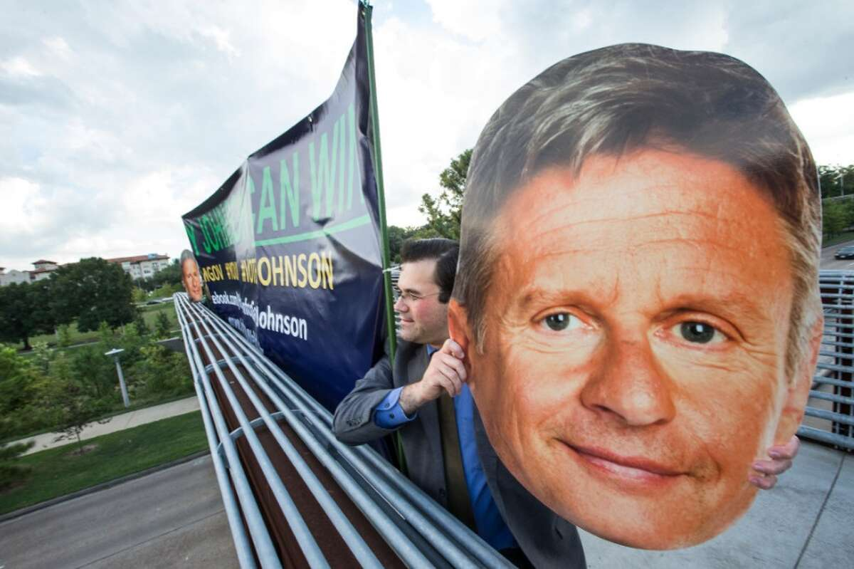 Gary Johnson supporters hold up signs while campaigning for the Libertarian Party nominee for President of the United Sates, on the Rosemont Pedestrian Bridge, that spans Memorial Drive, on Thursday, Sept. 15, 2016, in Houston.